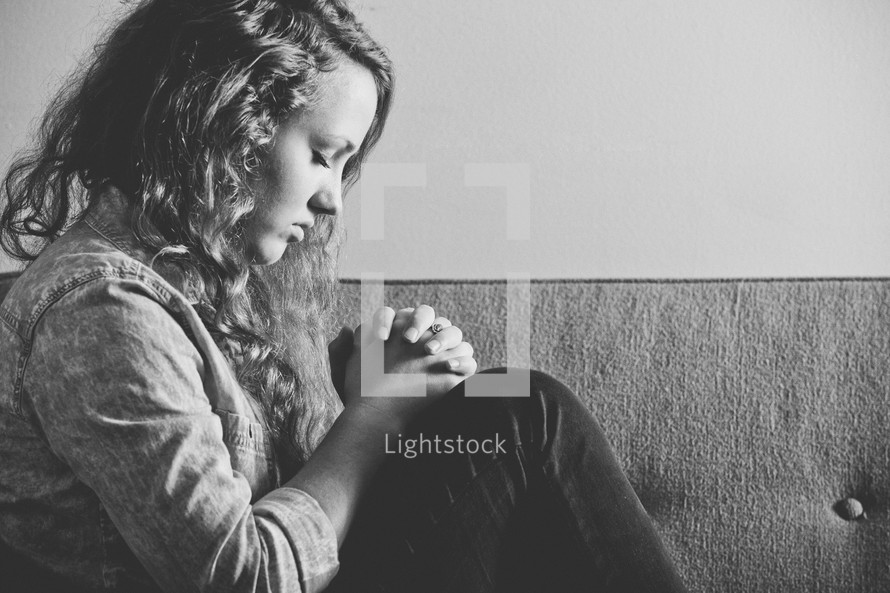 Woman in prayer while sitting on a couch.