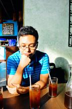 a man thinking sitting at a table at a restaurant