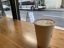 coffee cup on a table and view of a city bus