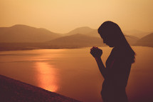 silhouette of a woman praying by a lake at sunset