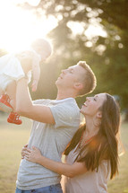 Couple holding infant child up to the sun.