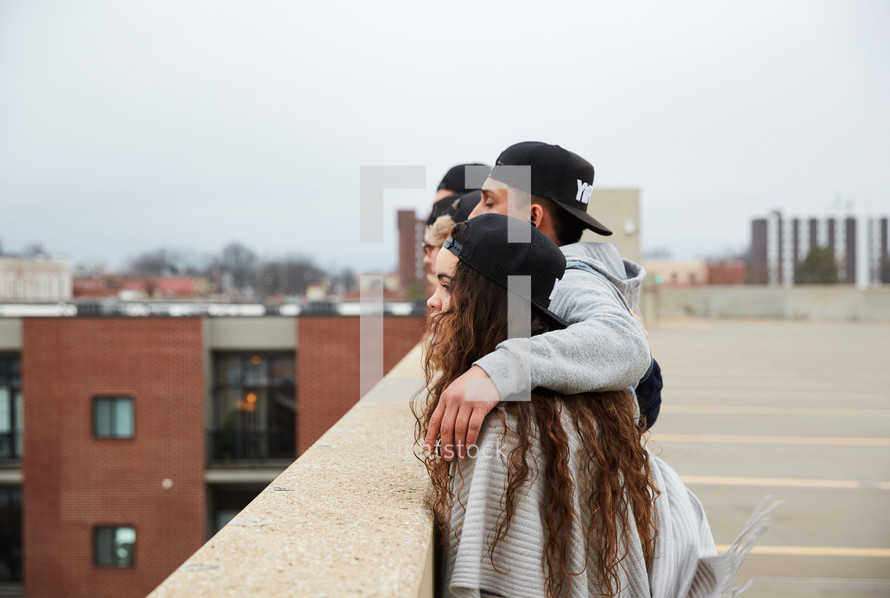 group of young people looking over a railing on a parking deck