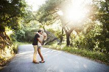 couple standing in the middle of a country road hugging