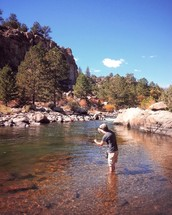 a man fly fishing in a river