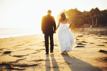 bride and groom walking holding hands on a beach