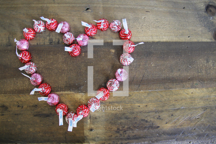 Hersey Kisses in a heart shape on a wood background