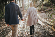 a couple walking through the woods holding hands