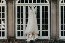 wedding dress hanging in a window