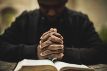 Man praying over Bible