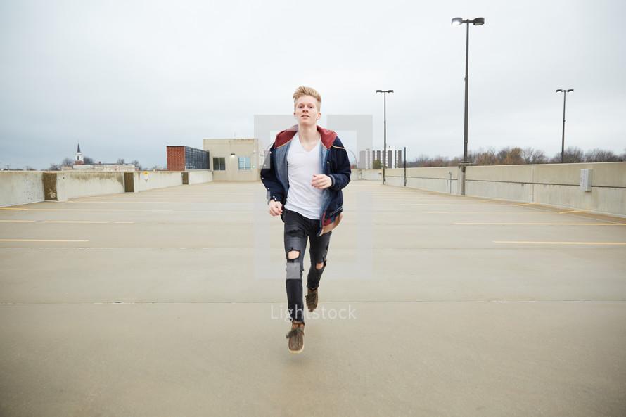 teen boy running in a parking deck