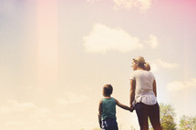 a mother and son holding hands outdoors.
