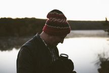 man in a wool cap standing by a lake holding a camera