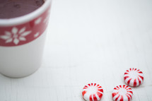 Peppermint candies and a cup of hot chocolate in a Christmas cup on a white table.