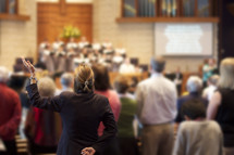 Women praising with hands raised from back of congregation.