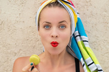 woman with her hair wrapped in a towel holding a macaron