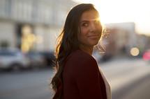 a woman walking down a city sidewalk at sunset.