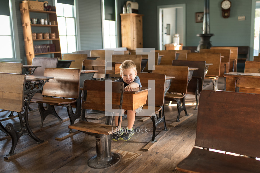 a toddler boy sitting in a desk of an old school house