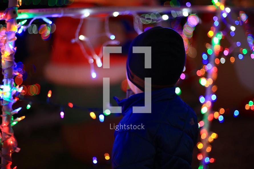 a boy admiring Christmas lights