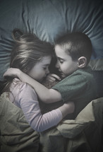 brother and sister cuddling sleeping
