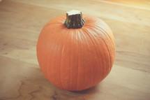 orange pumpkin on a wood background