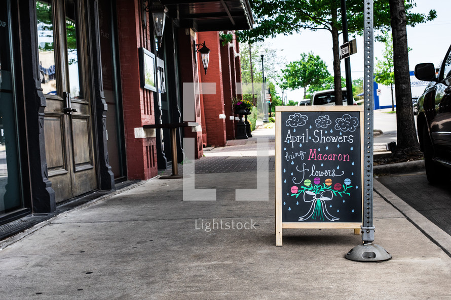 April Showers bring Macaron flowers sign on a downtown sidewalk