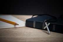 pencil, notepad, Bible, and cross necklace on a desk