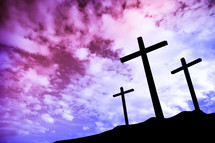 silhouettes of three crosses at sunrise