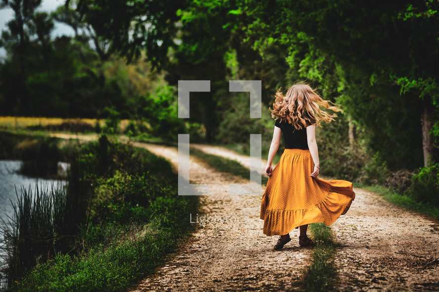 Girl with long hair in flowing skirt joyously twirling around with freedom in a country landscape with dirt road and pond.