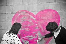 Couple painting a heart on a brick wall.
