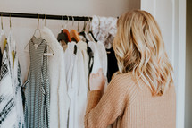 a woman looking at clothes in her closet