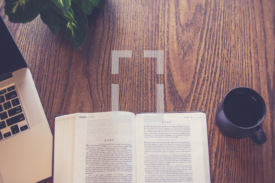 A Bible open to Luke, a cup of coffee and a computer on a wooden table.