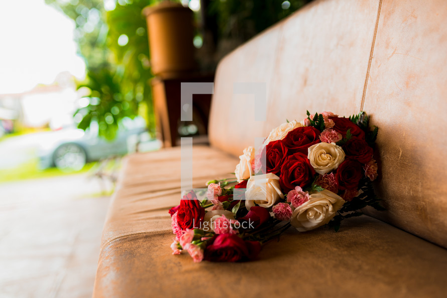 bouquet of roses on a leather bench