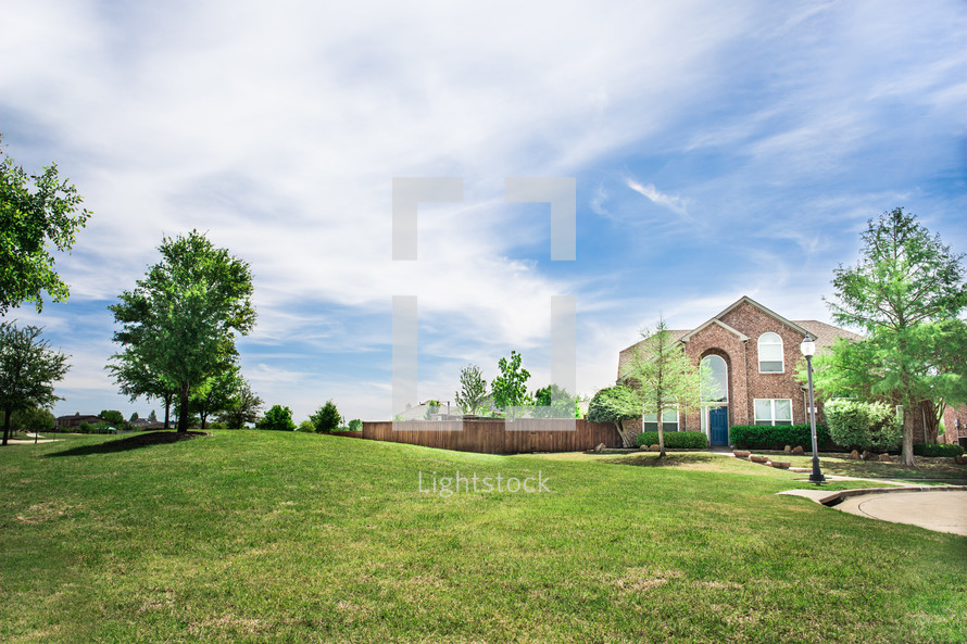 green grass in a front yard and brick house