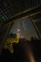 view of stars in a night sky through a barn door