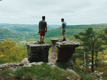 Two men stand on rock pinnacles overlooking a valley and forested hills.