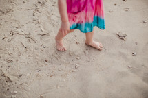 toddler girl walking in sand