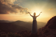 Woman on a hillside with arms raised in praise at daybreak.