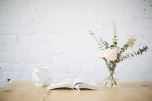 vase of flowers, open Bible, and coffee cup on a table