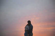 A man and woman embrace in front of a sunset.