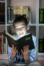 Kid reading the Holy Bible