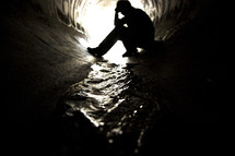 Silhouette of a man sitting with head in hands in a graffit-painted sewer drain pipe with water flowing through it.