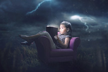 A little girl is scared and reading during a storm
