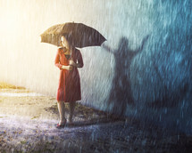 A woman caught in a rain storm with a different shadow