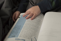 a toddler flipping through the pages of a Bible