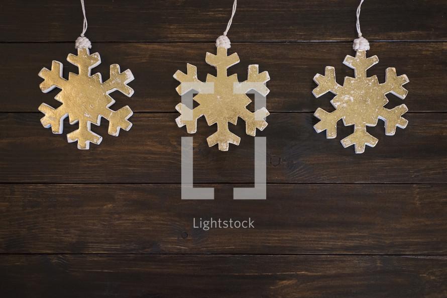 snowflake ornaments on a wood floor