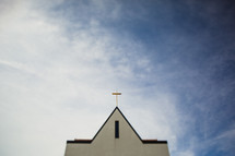 Steeple of a church with a cross in the sky.