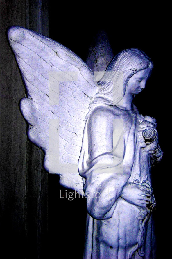 A pensive statue of an Angel with outspread wings guarding over a dearly departed loved one.