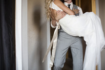 groom carrying his bride over the threshold