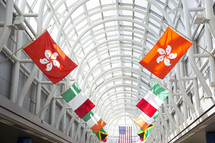 flags of various nations in an airport walkway.