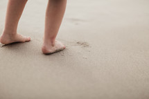 toddler's feet on a sandy beach